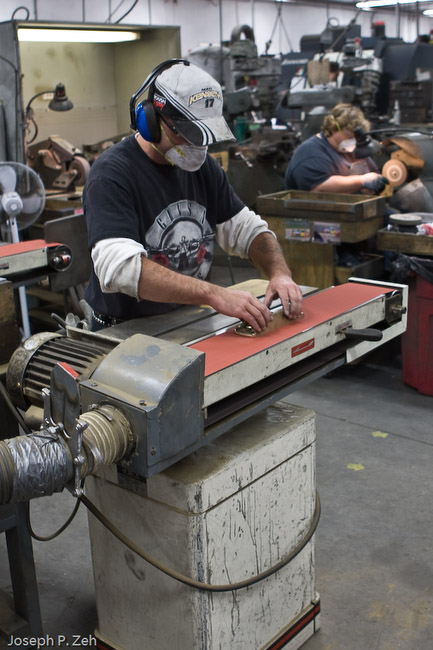 A member of the Bronze Group lapping the sole of a bronze plane by hand on a belt sander. All LN planes are held to a .001 inch tolerance for flatness.
