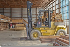 The fork lift always stands ready to access a pallet of lumber not yet graded.